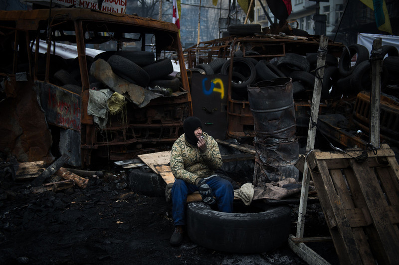 Description of  An anti-government protester smokes sitting on a tyre by a barricade in Kiev, on February 15, 2014. Ukraine's political situation has been volatile since a massive protest movement erupted in November when Ukraine President Viktor Yanukovych rejected a key EU trade pact in favour of closer ties with Russia, angering pro-EU parts of the population. The movement has since evolved into an outright drive to oust Yanukovych, while protesters still  occupy Kiev's central Independence square. (MARTIN BUREAU/AFP/Getty Images)