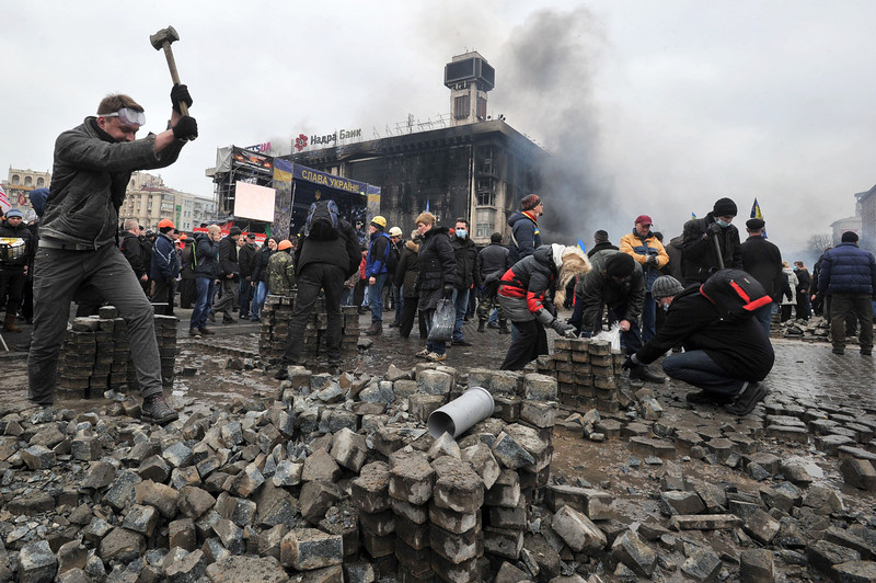 Description of  Anti-government protesters dig up cobblestones to use them as rocks against riot police on Kiev's Independence square on February 19, 2014. Protesters braced on February 19 for a fresh assault by riot police in central Kiev after a day of clashes left at least 25 people dead in the worst violence since the start of Ukraine's three-month political crisis. As dawn rose over Kiev's battered city centre, protesters hurled paving stones and Molotov cocktails at lines of riot police that had pushed into the heart of the devastated protest camp on Independence Square. (GENYA SAVILOV/AFP/Getty Images)