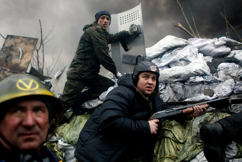 Description of  An anti-government protester holds a firearm as he mans a barricade on the outskirts of Independence Square in Kiev, Ukraine, Thursday, Feb. 20, 2014. Fierce clashes between police and protesters, some including gunfire, shattered a brief truce in Ukraine's besieged capital Thursday, killing numerous people. The deaths came in a new eruption of violence just hours after the country's embattled president and the opposition leaders demanding his resignation called for a truce and negotiations to try to resolve Ukraine's political crisis. (AP Photo/ Marko Drobnjakovic)