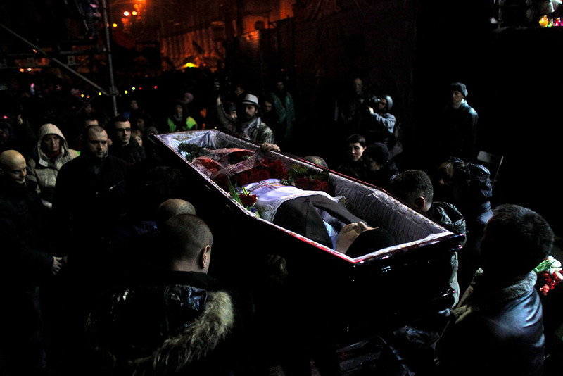 Description of  A body of an anti-government protester, killed in clashes with police,  is brought to Independence Square in Kiev, Ukraine, Saturday, Feb. 22, 2014. Protesters took control of Ukraine's capital Saturday, seizing the president's office as parliament voted to remove him and hold new elections. (AP Photo/ Marko Drobnjakovic)