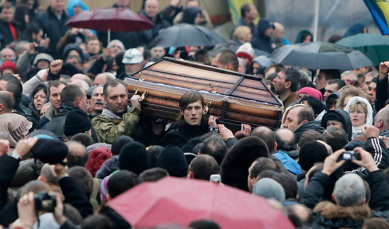 Description of  A coffin with the body of a protester killed in recent clashes is carried through the crowd in central Kiev, Ukraine, Saturday, Feb. 22, 2014. Protesters in the Ukrainian capital claimed full control of the city Saturday following the signing of a Western-brokered peace deal aimed at ending the nation's three-month political crisis. The nation's embattled president, Viktor Yanukovych, reportedly had fled the capital for his support base in Ukraine's Russia-leaning east. (AP Photo/Efrem Lukatsky)