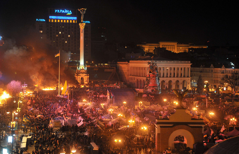 Description of  Anti-government protesters clash with the police during their storming of the Independence Square in Kiev on February 18, 2014. Flames engulfed the main anti-government protest camp on Kiev's Independence Square on Tuesday as riot police tried to force demonstrators out following the bloodiest clashes in three months of protests. The iconic square turned into a war zone as riot police moved slowly through opposition barricades from several directions, hurling stun grenades and using water cannon to clear protestors.  (GENYA SAVILOV/AFP/Getty Images)