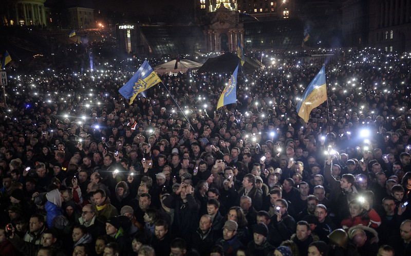 Description of  Anti-government protesters gather on the Independent square in Kiev on February 21, 2014. The Ukrainian President Viktor Yanukovych and three main opposition leaders signed a deal on February 21 to end a three-month crisis over the ex-Soviet country's political future that has led to nearly 100 deaths. The pact paving the way for early elections and a shift in political power toward parliament was signed in the Blue Hall of the presidential palace in the presence of three EU envoys, an AFP correspondent said. BULENT KILIC/AFP/Getty Images