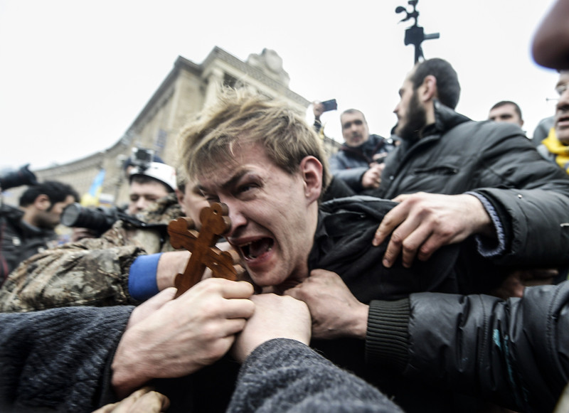 Description of  An alleged sniper (C) and member of the pro-government forces is beaten by anti-government protestors in Kiev on February 22, 2014. The regime of Ukraine's president appeared close to collapse on February 22 as the emboldened opposition took control of central Kiev and key government and parliament positions and voted to immediately free its jailed leader Yulia Tymoshenko. BULENT KILIC/AFP/Getty Images