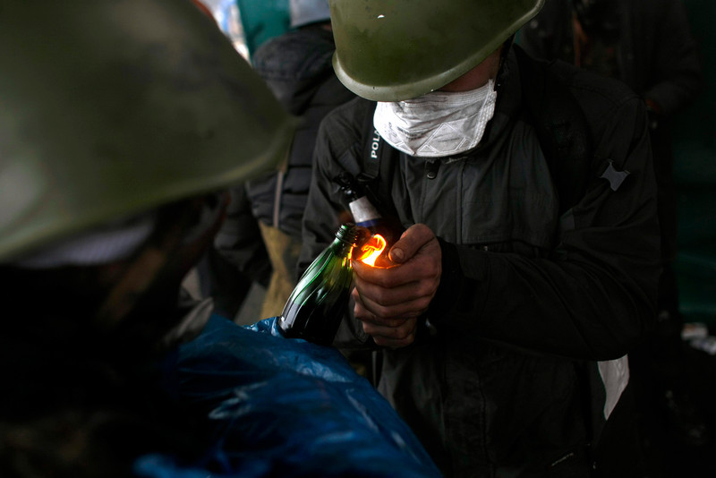 Description of  Anti-government protesters light petrol bombs on the outskirts of Independence Square in Kiev, Ukraine, Thursday, Feb. 20, 2014. Fierce clashes between police and protesters, some including gunfire, shattered a brief truce in Ukraine's besieged capital Thursday, killing numerous people. The deaths came in a new eruption of violence just hours after the country's embattled president and the opposition leaders demanding his resignation called for a truce and negotiations to try to resolve Ukraine's political crisis.  (AP Photo/ Marko Drobnjakovic)