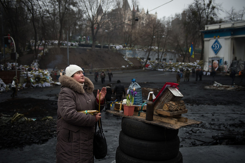 Description of  A woman prays by a makeshift shrine in Kiev, on February 15, 2014. Ukraine's political situation has been volatile since a massive protest movement erupted in November when Ukraine President Viktor Yanukovych rejected a key EU trade pact in favour of closer ties with Russia, angering pro-EU parts of the population. The movement has since evolved into an outright drive to oust Yanukovych, while protesters still  occupy Kiev's central Independence square. (MARTIN BUREAU/AFP/Getty Images)