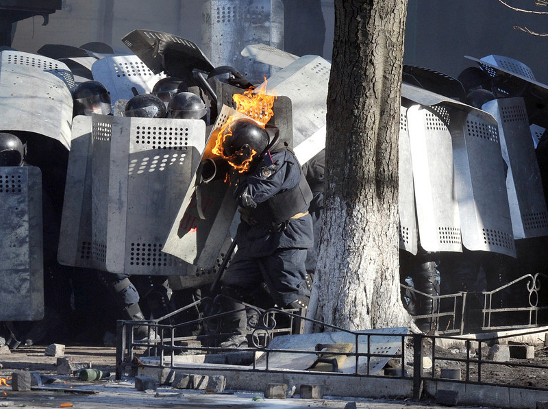 Description of  A photo taken on February 18, 2014 shows a riot police whose helmet is burning, shielding himself during clashes with anti-government protesters in central Kiev. At least five people were killed and scores injured on February 18 as anti-government protestors battled riot police in Kiev in the first outbreak of violence in weeks. Police said five civilians have died in clashes that prompted the city to shut down the subway system and issued a grave warning to protesters, with riot police troops massing near the Independence Square protest hub. (GENYA SAVILOV/AFP/Getty Images)