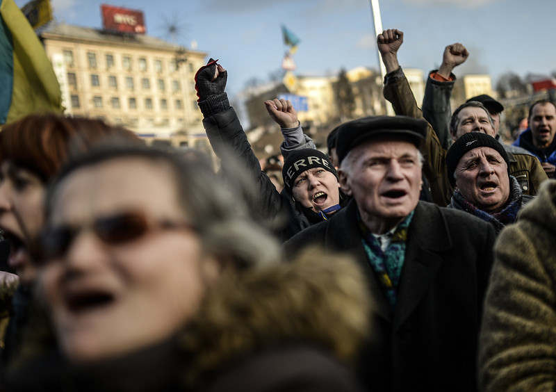 Description of  Anti government protesters chant slogans on Independence square on February 21, 2014 in Kiev.  Ukrainian President Viktor Yanukovych and three main opposition leaders signed a deal Friday to end a three-month crisis over the ex-Soviet country's political future that has led to nearly 100 deaths. The pact paving the way for early elections and a shift in political power toward parliament was signed in the Blue Hall of the presidential palace in the presence of three EU envoys, an AFP correspondent said. BULENT KILIC/AFP/Getty Images