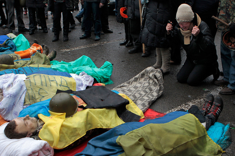 Description of  Activists pay respects to protesters killed in clashes with police, in Kiev's Independence Square, the epicenter of the country's current unrest, Thursday, Feb. 20, 2014. Fierce clashes between police and protesters, some including gunfire, shattered a brief truce in Ukraine's besieged capital Thursday, killing numerous people. The deaths came in a new eruption of violence just hours after the country's embattled president and the opposition leaders demanding his resignation called for a truce and negotiations to try to resolve Ukraine's political crisis. (AP Photo/Sergei Chuzavkov)