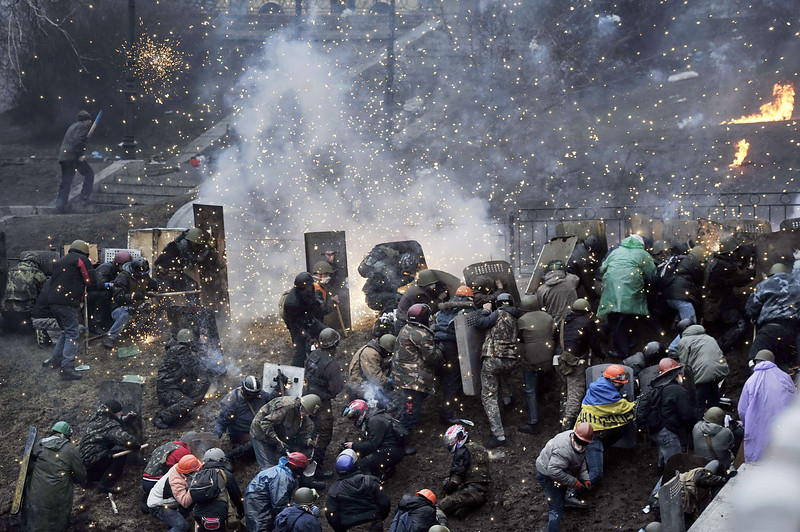 Description of  Protesters clash with police after gaining new positions near the Independence square in Kiev on February 20, 2014. Hundreds of armed protesters charged police barricades Thursday on Kiev's central Independence Square, despite a truce called just hours earlier by the country's embattled president. Protesters pushed the police back about 200 meters and were in control of most of the square they had occupied at the start of Ukraine's three-month-old political crisis. (LOUISA GOULIAMAKI/AFP/Getty Images)