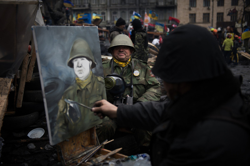 Description of  An artist paints the portrait of an anti-government protester wearing a full military outfit on a barricade in Kiev, on February 16, 2014. Ukraine's political situation has been volatile since a massive protest movement erupted in November when Ukraine President Viktor Yanukovych rejected a key EU trade pact in favour of closer ties with Russia, angering pro-EU parts of the population. The movement has since evolved into an outright drive to oust Yanukovych, while protesters still occupy Kiev's central Independence square. (MARTIN BUREAU/AFP/Getty Images)