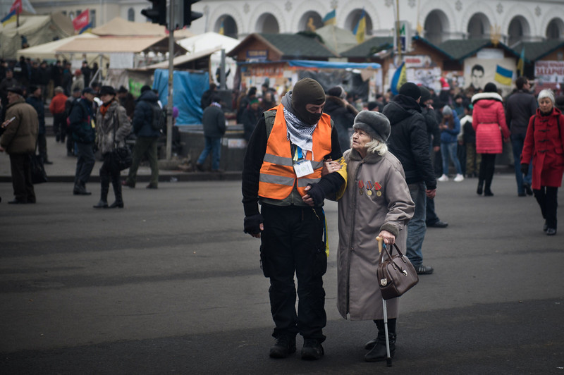 Description of  An anti-government protester talks to an elderly woman on the Maidan (Independence square) in Kiev, on February 15, 2014. Ukraine's political situation has been volatile since a massive protest movement erupted in November when Ukraine President Viktor Yanukovych rejected a key EU trade pact in favour of closer ties with Russia, angering pro-EU parts of the population. The movement has since evolved into an outright drive to oust Yanukovych, while protesters still  occupy Kiev's central Independence square. (MARTIN BUREAU/AFP/Getty Images)