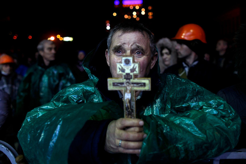 "Description of  An anti-government protester holds a crucifix as he prays at Independence Square in Kiev, Ukraine, Thursday, Feb. 20, 2014. Ukraine's protest leaders and the president they aim to oust called a truce Wednesday, just hours after the military raised fears of a widespread crackdown with a vow to defeat ""terrorists"" responsible for seizing weapons and burning down buildings. (AP Photo/ Marko Drobnjakovic)"