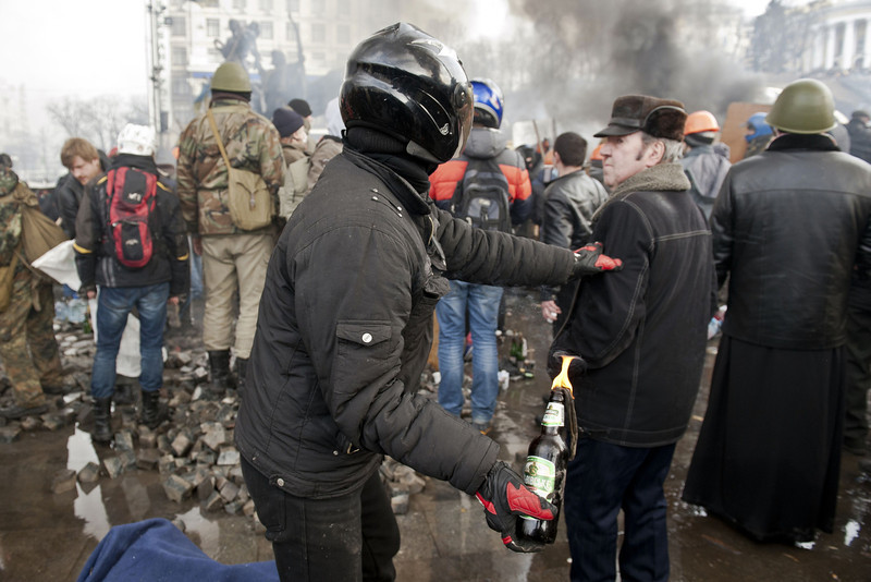 Description of  A anti-government protester prepares to throw a Molotov cocktail at riot police on Kiev's Independence square on February 19, 2014. Protesters braced on February 19 for a fresh assault by riot police in central Kiev after a day of clashes left at least 25 people dead in the worst violence since the start of Ukraine's three-month political crisis. As dawn rose over Kiev's battered city centre, protesters hurled paving stones and Molotov cocktails at lines of riot police that had pushed into the heart of the devastated protest camp on Independence Square. (PIERO QUARANTA/AFP/Getty Images)