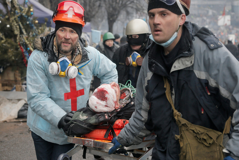 Description of  Activists  evacuate a wounded protester during clashes with police in Kiev's Independence Square, the epicenter of the country's current unrest, Kiev, Ukraine, Thursday, Feb. 20, 2014. Fierce clashes between police and protesters, some including gunfire, shattered a brief truce in Ukraine's besieged capital Thursday, killing numerous people. The deaths came in a new eruption of violence just hours after the country's embattled president and the opposition leaders demanding his resignation called for a truce and negotiations to try to resolve Ukraine's political crisis.   (AP Photo/Efrem Lukatsky)