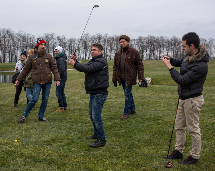Description of  Protesters try to play on a golf course at the Ukrainian President Yanukovych's countryside residence in Mezhyhirya, Kiev's region, Ukraine, Saturday, Feb, 22, 2014. Viktor Yanukovych is not in his official residence of Mezhyhirya, which is about 20 kilometres north of the capital. Ukrainian security and volunteers from among Independence Square protesters have joined forces to protect the presidential countryside retreat from vandalism and looting.(AP Photo/Andrew Lubimov)