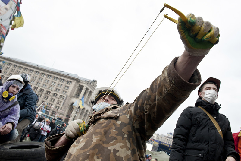 Description of  An anti-government protester uses a slingshot to throw stones towards riot police on Kiev's Independence square on February 19, 2014. Protesters braced on February 19 for a fresh assault by riot police in central Kiev after a day of clashes left at least 25 people dead in the worst violence since the start of Ukraine's three-month political crisis. As dawn rose over Kiev's battered city centre, protesters hurled paving stones and Molotov cocktails at lines of riot police that had pushed into the heart of the devastated protest camp on Independence Square.  (PIERO QUARANTA/AFP/Getty Images)
