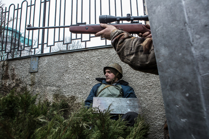 Description of  An anti-government protester aims a gun in the direction of suspected sniper fire near the Hotel Ukraine on February 20, 2014 in Kiev, Ukraine. After several weeks of calm, violence has again flared between anti-government protesters and police, with dozens killed. (Photo by Brendan Hoffman/Getty Images)