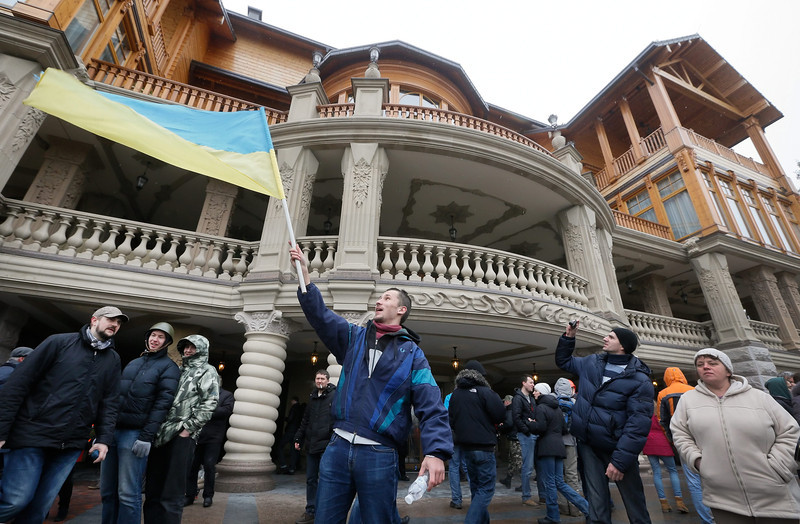 Description of  An Ukrainian waves a national flag as he poses in front on of the main buildings in the residence of Ukrainian President Viktor Yanukovych in the Mezhyhirya village near Kiev, Ukraine, 22 February 2014. Protesters took full control of the Yanukovych residence and provided free access of the premises for Ukrainian and the media. Ukrainian President Viktor Yanukovych and security forces deserted the capital Kiev as protesters on 22 February moved  to secure state institutions and parliament took steps towards forming a transitional government.  EPA/SERGEY DOLZHENKO
