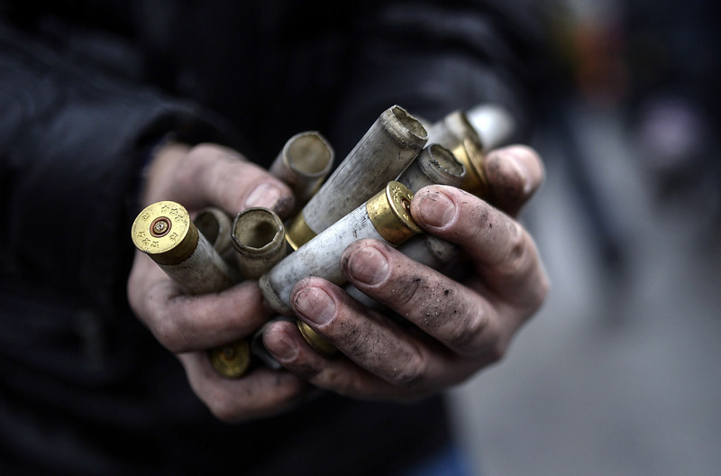 Description of  An anti-government protester shows empty bullet casings used by riot police against demonstrators in central Kiev on February 20, 2014. At least 25 protesters were killed on February 20 in fresh clashes between thousands of demonstrators and heavily-armed riot police in the heart of Kiev, AFP correspondents at the scene said. The bodies of eight demonstrators were lying outside Kiev's main post office on Independence Square, an AFP reporter said. The bodies of 17 other demonstrators with apparent gunshot wounds were also seen in the vicinity of two hotels on opposite sides of the protest encampment. (BULENT KILIC/AFP/Getty Images)
