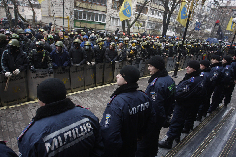 "Description of  Anti-government protestors of the ""14 Hundred Self-Defense"" group face police as they take part in a protest rally in front of the Prosecutor General building in Kiev on February 14, 2014. Protesters armed with shields and clubs demanded the government stop prosecuting cases against anti-government activists involved in clashes with police.  (YURY KIRNICHNY/AFP/Getty Images)"