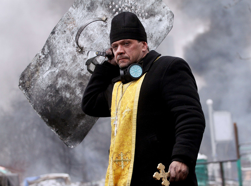 Description of  A priest holds a cross and shield during clashes between anti-government protesters and riot police in central Kiev on February 20, 2014. Ukraine's brittle truce was shattered on February 20 in fierce clashes between baton-wielding protesters and riot police that claimed at least 27 lives just as EU envoys were holding crisis talks with the embattled president. Bodies of anti-government demonstrators lay amid smoldering debris after masked protesters hurling Molotov cocktails and stones forced gun-toting police from Kiev's iconic Independence Square -- the epicentre of the ex-Soviet country's three-month-old crisis. (SERGEY GAPON/AFP/Getty Images)