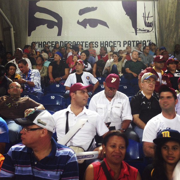 Description of  People are sitting in front of an image depicting the eyes of late Venezuelan former President Hugo Chavez during a baseball Caribbean Series game in Nueva Esparta state, Venezuela on February 07, 2014. A year after the death of President Hugo Chavez, the image that depicts his eyes are seen everywhere, from giant billboards and buildings to t-shirts and notebooks. This photo was taken with a mobile phone. LEO RAMIREZ/AFP/Getty Images