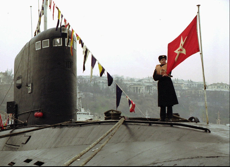 Description of  Black Sea Fleet sailor adjusts a former Soviet navy flag atop a fleet submarine, Wednesday, March 20, 1996 at the Sevastopol naval base, the Crimea, Ukraine. Russia and Ukraine so far have failed to divide their shares of the fleet ships, which still carry old Soviet naval flags along with Russian ones. (AP Photo/Sergei Volkov)