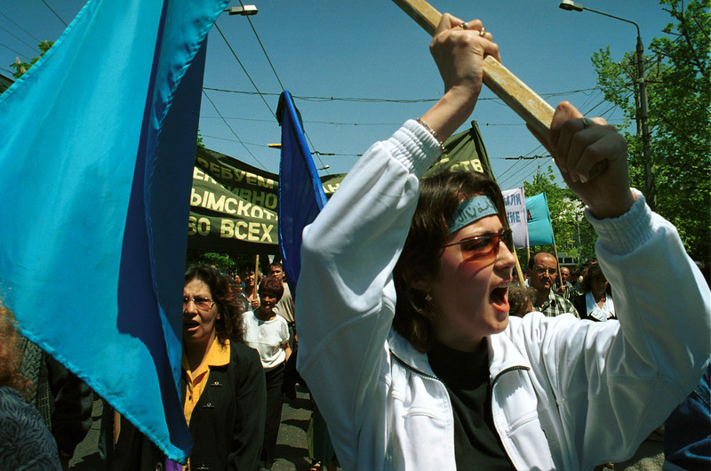 Description of  SIMFEROPOL, UKRAINE - MAY 18:   A woman carries a flag during a demonstration for the Crimean Tartars May 18, 2003 in Simferopol, Ukraine. The demonstration marked the 59th anniversary of a mass deportation by Stalin's regime during World War II of the Crimean Tarters, the name given to Turkic people living in the Crimean Peninsula in what is now the Ukraine. Approximately 15,000 participants took part in this demonstration.  (Photo by Sergei Svetlitsky/Getty Images)