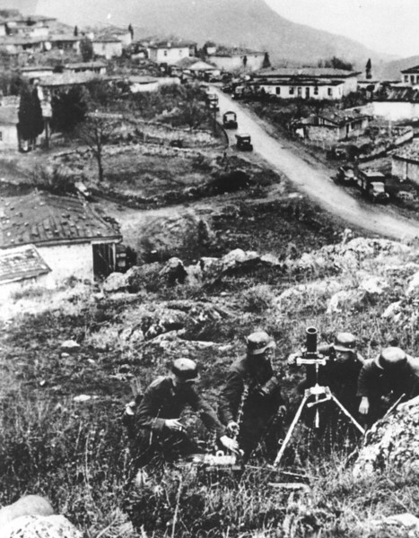 Description of  As the  German invasion of the southern Ukraine continues, soldiers of an advance division are seen at an unknown village, somewhere between the Crimean Mountains and the Black Sea, on March 12, 1941. A military convoy is moving down a street in the background. AP Photo)