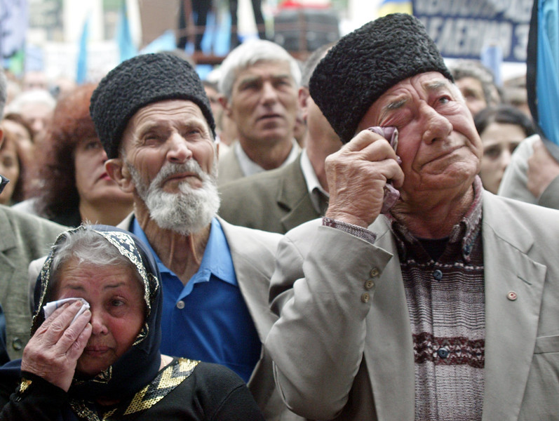 Description of  Crimean Tatars wipe their tears at a mourning rally during the 60th anniversary of deportation of ethnic Tatars under Soviet dictator Josef Stalin, in the Crimean capital of Simferopol, Ukraine, Tuesday, May 18, 2004. Thousands of people gathered in Simferopol main square to honor the memory of victims of the Soviet regime (AP Photo/Efrem Lukatsky)