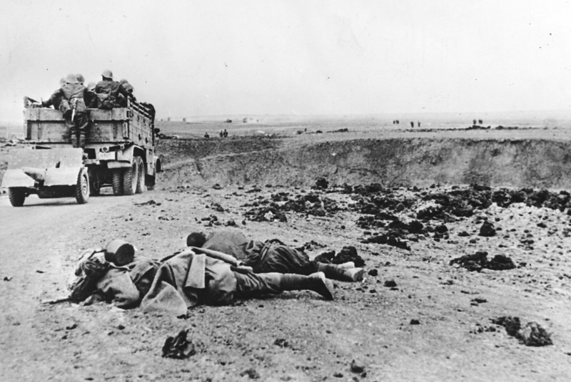 Description of  The bodies of two fallen Soviet soldiers lie at roadside, while a truck of the Romanian Army, with an artillery gun in tow, advances towards the city of Kerch, in June 1942, during the Battle of the Crimea in World War II. (AP Photo)