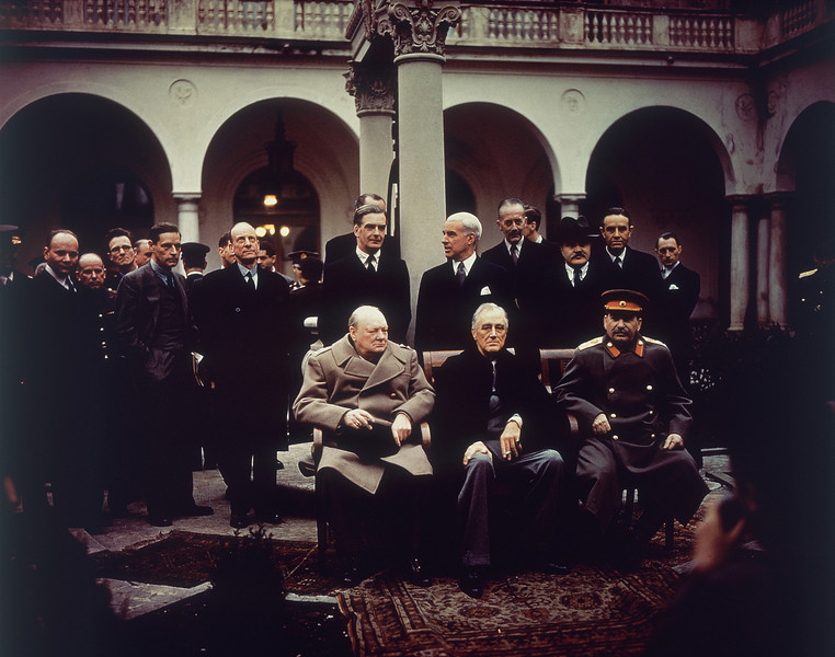 Description of  With their foreign secretaries behind them, British Prime Minister Winston Churchill, U.S. President Franklin Roosevelt and Soviet Premier Josef Stalin sit on the patio of Livadia Palace, Yalta, Crimea, Feb. 4, 1945.  Standing, from left: Foreign Sec. Anthony Eden, Sec. of State Edward R. Stettinius, and Foreign Commissar Vyasheslav Molotov. (AP Photo)