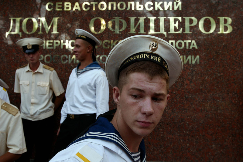 Description of  SEVASTOPOL, UKRAINE - AUGUST 15:  Russian sailors linger on a street August 15, 2003 in Sevastopol, Crimea in the Ukraine. Sevastopol is the main base of the Russian Black Sea Fleet. Russia and the Ukraine have an agreement keeping the base in Sevastopol through 2017.  (Photo by Oleg Nikishin/Getty Images)