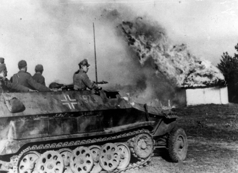 Description of  October 1942:  German troops making a dash to escape in the Crimea are cut off by Russian forces. An armoured personnel carrier is seen rushing through a burning Russian village on their way to the Dnieper River.  (Photo by Keystone/Getty Images)