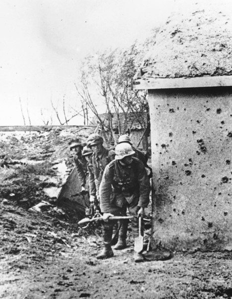Description of  As the German invasion of the Ukraine continues, soldiers of the invading Wehrmacht troops are seen in the cover of a shell-marked wall, at an unknown location on the Crimean peninsula, in November 1941. (AP Photo)