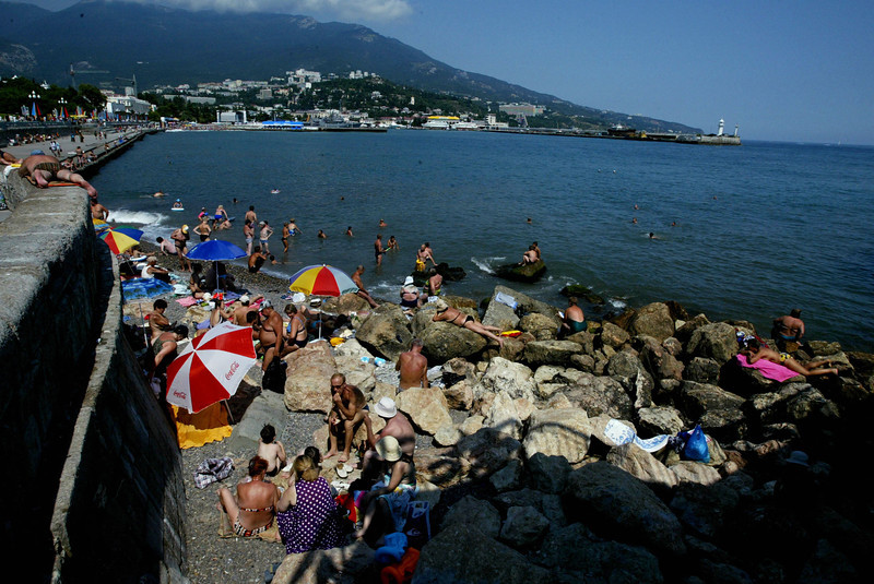 Description of  CRIMEA, UKRAINE - AUGUST 18:  Sunbathers lay out on the rugged beach of Yalta August 18, 2003 in Crimea, Ukraine. After the number of annual visitors to the Black Sea peninsula dropped from 8 million in the late Soviet era to just 3 million in the mid 1990's, about 4.5 million vacationers traveled to Crimea in 2002.  (Photo by Oleg Nikishin/Getty Images)