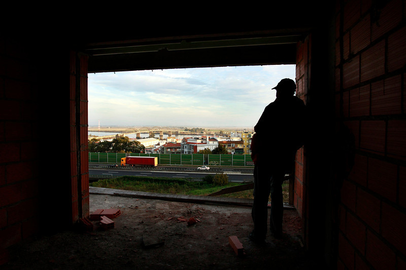 "Description of  Maciel looks over the city and the river from one of the unfinished condominium apartments. In mid-January he will fly to England in search of work. ""In Portugal there is no more hope for better days,"" he says.  (Photo by Bruno Colaço, Special to The Denver Post)"