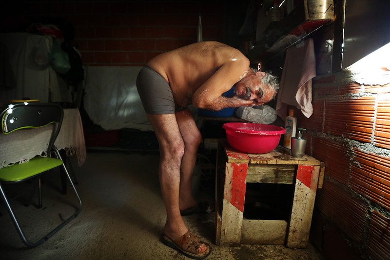 Description of  Manuel bathes using water heated with a small gas bowl. With no electricity, no piped water and no bathroom the residents had to make adaptions to some of their most common day-to-day tasks.  (Photo by Bruno Colaço, Special to The Denver Post)