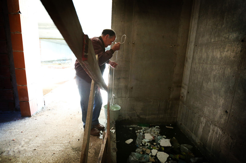 Description of  Manuel fills a bucket with water in the elevator shaft of the condo which collects water from the rain and serves as a reservoir to the people living in the empty building. Manuel uses this water for all purposes except to drink.  (Photo by Bruno Colaço, Special to The Denver Post)