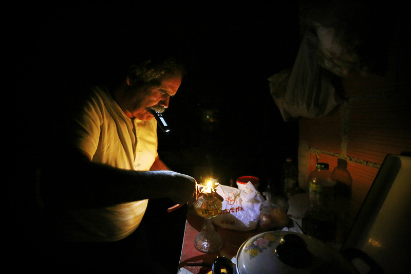 Description of  Manuel tries to fix an oil lamp while using his phone as a flashlight. Manuel worked for many years in many countries in the construction sector. His family still believes that he is working somewhere in Germany.  (Photo by Bruno Colaço, Special to The Denver Post)