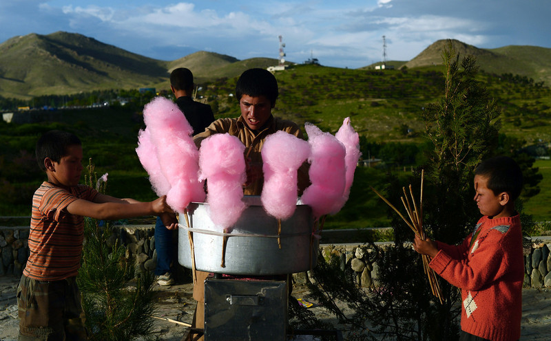 Description of  Afghan children buy candy floss from a street vendor near Qargha Lake in the outskirts of Kabul on May 9, 2014. Qargha Lake, located 9 kms outside of Kabul, is a popular recreational spot and known for its swimming and boating activities. WAKIL KOHSAR/AFP/Getty Images