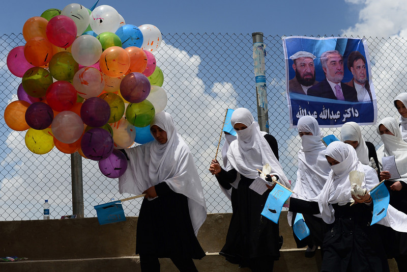 Description of  Afghan schoolgirls holds balloons and flags as they attend an election rally by presidential candidate Abdullah Abdullah in Gardez, capital of eastern Paktia province on May 24, 2014. Afghan presidential candidates Abdullah Abdullah and Ashraf Ghani will compete in the run-off on June 14 to determine who leads Afghanistan into a new era without the assistance of NATO combat troops to help fight the Taliban insurgency. WAKIL KOHSAR/AFP/Getty Images