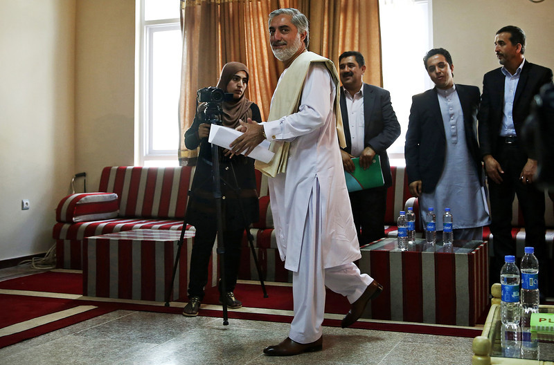 Description of  Afghan presidential candidate Abdullah Abdullah arrives for a news conference in Kabul, Afghanistan, Wednesday, May 14, 2014. Front-runner Abdullah says that still there is time for the Elections Complain Commission to continue to their assessments ahead of the final election result announcements regarding the concerns over 1433 ballot boxes across the country and this assessment would have impact on the final results. (AP Photo/Massoud Hossaini)
