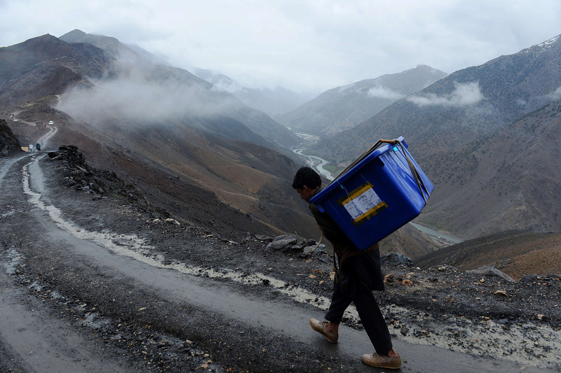 Description of  An Afghan villager carries election materials over his shoulders as he hikes back to his village along a country road high in the mountains of Shutul District in northern Afghanistan on April 4, 2014.  Afghans will vote on April 5 in the country's third presidential election to choose a successor to Hamid Karzai, who has led the country since the fall of the Taliban in 2001. SHAH MARAI/AFP/Getty Images