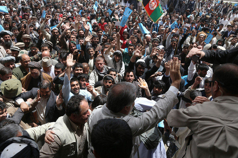 Description of  Afghan presidential candidate Abdullah Abdullah, center, back to camera, arrives at a campaign rally in Paktiya province, east of Kabul, Afghanistan, Saturday, May 24, 2014. The campaign season for the second round of Afghanistan's presidential election kicked off on Thursday. (AP Photo/Rahmat Gul)