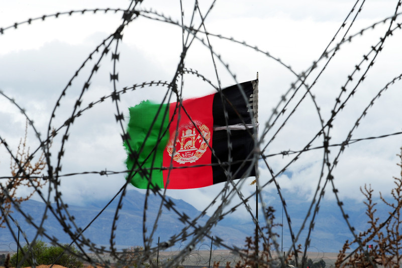 Description of  In this picture taken on March 17, 2014, the Afghan national flag flutters in the wind behind barbed wire at a forward operating base where soldiers attached to the 4th Brigade, 201 Army Corps of the Afghan National Army (ANA) live in Khogyani district. In the eastern district of Khogyani, the war against Taliban militants is a day-to-day struggle for control of fields and villages just outside Jalalabad, one of Afghanistan's biggest and most strategic cities. ROBERTO SCHMIDT/AFP/Getty Images