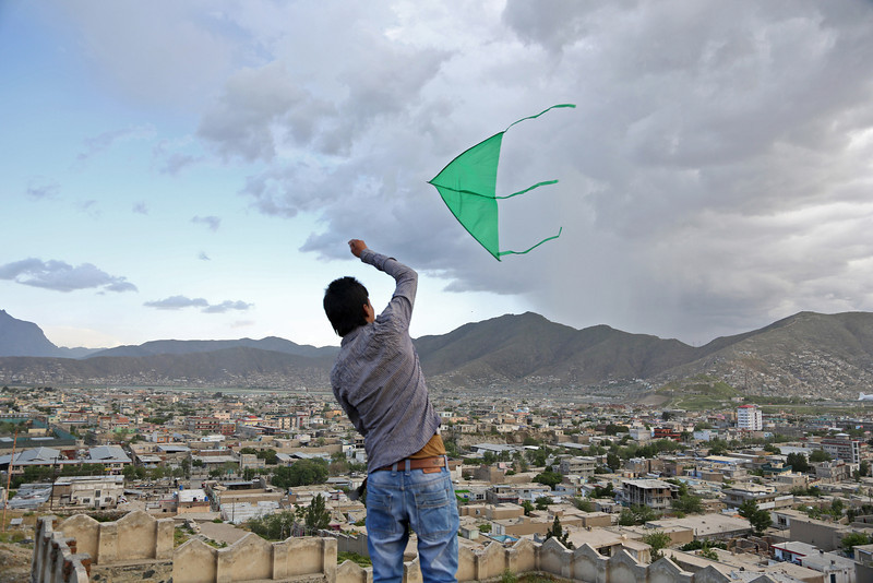 Description of  An Afghan boy flies a kite on the Nadir Khan hilltop in Kabul, Afghanistan, Friday, May 9, 2014. Kite flying is a popular pastime in Afghanistan, where opponents go after the kite wafting in the air after its line gets cut by another player in the so-called kite fighting.(AP Photo/Rahmat Gul)