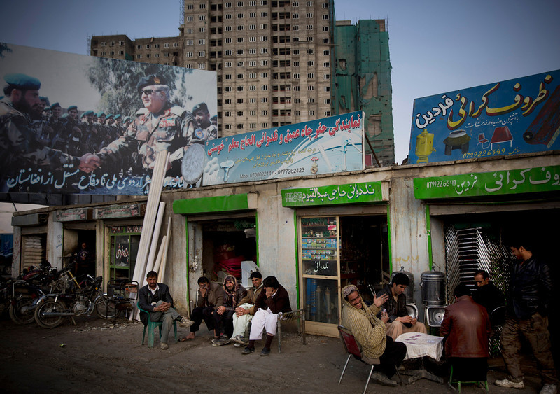 Description of  In this Monday, March 17, 2014 photo, Afghan men play cards under a huge election poster showing Abdul Rahim Wardak, Afghanistanís former defense minister, shaking hands with soldiers in Kabul, Afghanistan. Wardak pulled out of the presidential elections, but warlords with a violent past have played a role in influencing Afghan politics since a U.S.-led coalition helped oust the Taliban in 2001. But they are emerging to play an overt political role in next monthís presidential elections as President Hamid Karzai leaves the scene. (AP Photo/Anja Niedringhaus)  - Niedringhaus, 48, was killed and an AP reporter was wounded on Friday, April 4, 2014 when an Afghan policeman opened fire while they were sitting in their car in eastern Afghanistan.