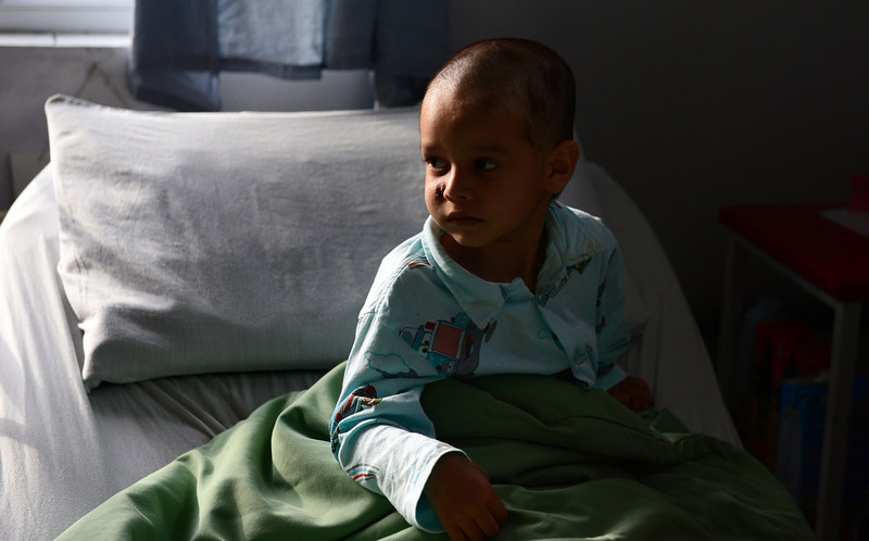 Description of  In this file photograph taken on April 6, 2014, Abuzar Ahmad, the youngest son of slain Afghan AFP reporter Sardar Ahmad, sits in bed during a visit by family members at a local hospital in Kabul.  Six weeks after surviving a Taliban attack on a Kabul hotel that left his father, mother, brother and sister dead, miracle child Abuzar Ahmad arrived in Canada on April 30, 2014 to start his life anew. WAKIL KOHSAR/AFP/Getty Images